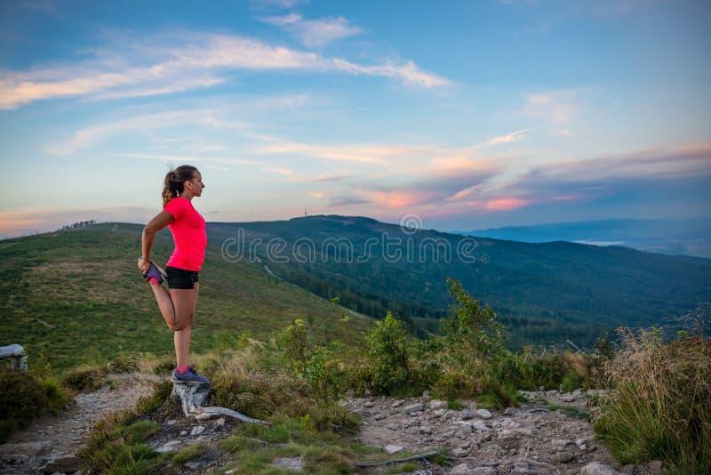Donna che allunga dopo il funzionamento della traccia in montagne immagini stock libere da diritti