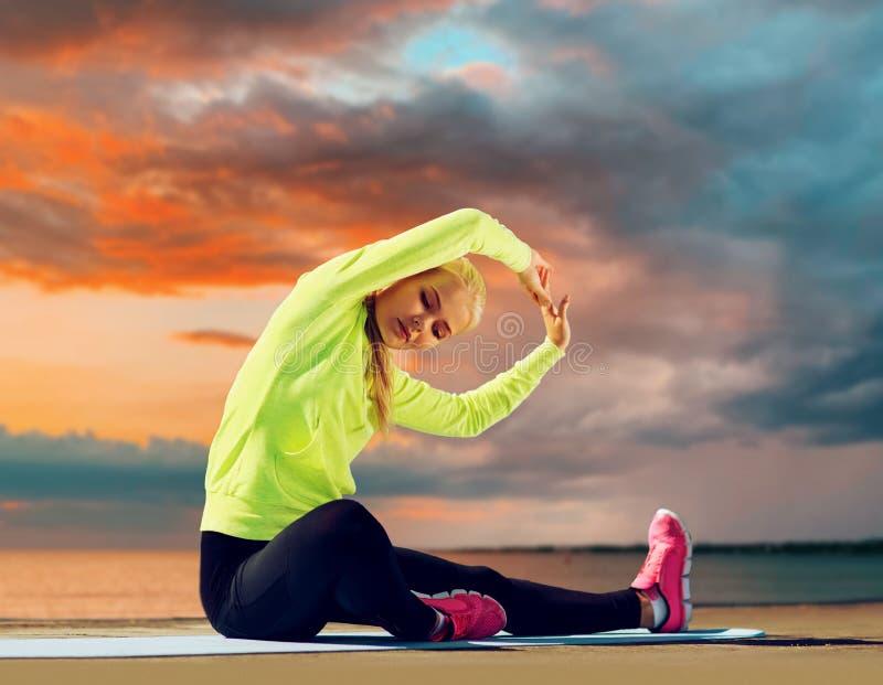 Donna che allunga sulla stuoia di esercizio alla spiaggia immagini stock