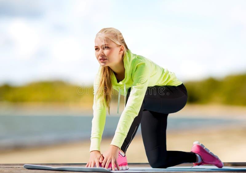 Donna che allunga sulla stuoia di esercizio sulla spiaggia immagini stock libere da diritti