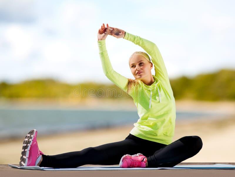 Donna che allunga sulla stuoia di esercizio sulla spiaggia fotografia stock
