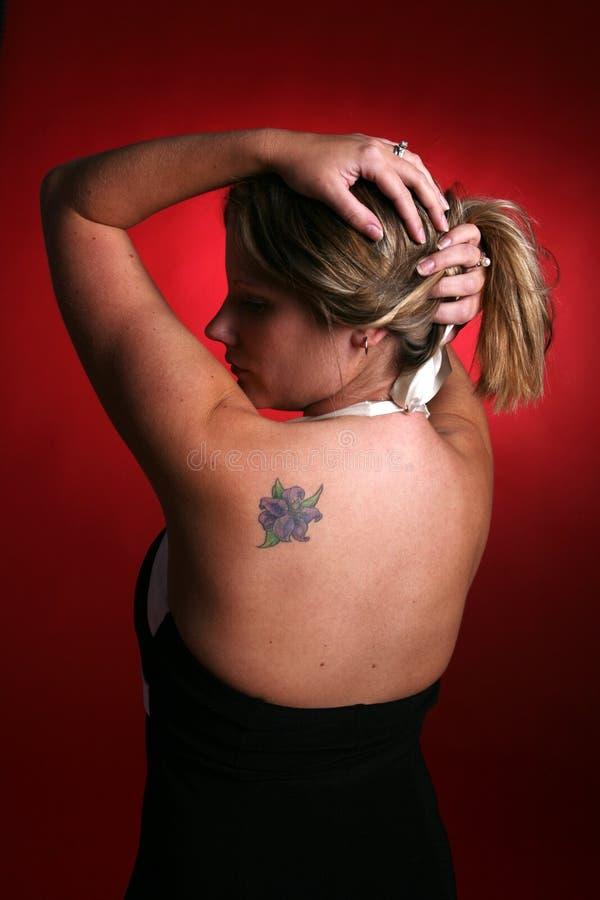 Donna che alza i suoi capelli e che mostra il suo tatuaggio fotografie stock libere da diritti