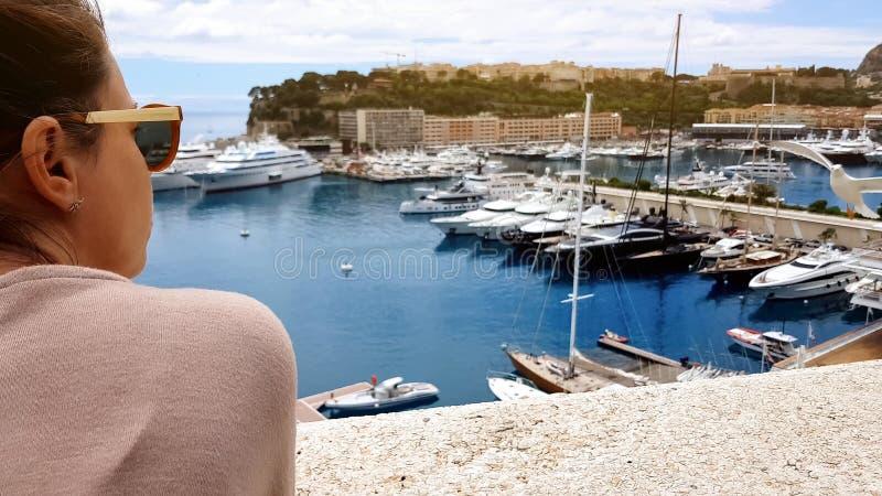 Donna che ammira vista sul mare con gli yacht, gabbiani che pilotano resto vicino e piacevole immagini stock
