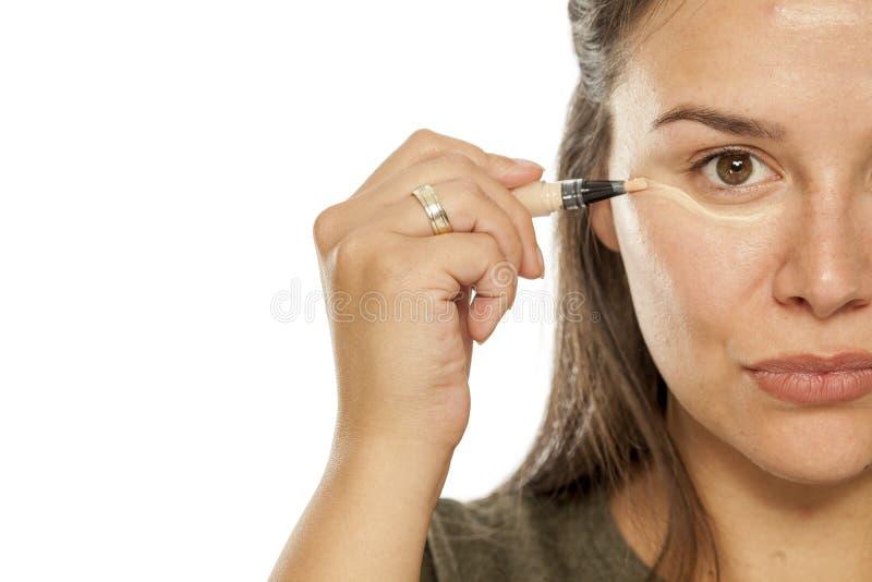 Donna che applica concealer immagini stock