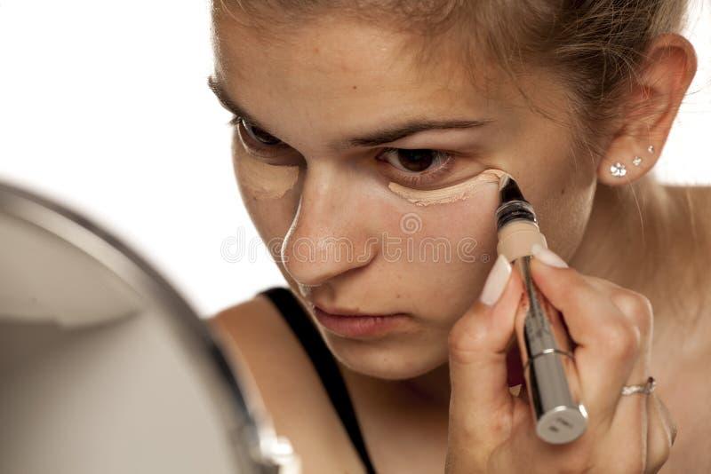 Donna che applica concealer fotografia stock libera da diritti