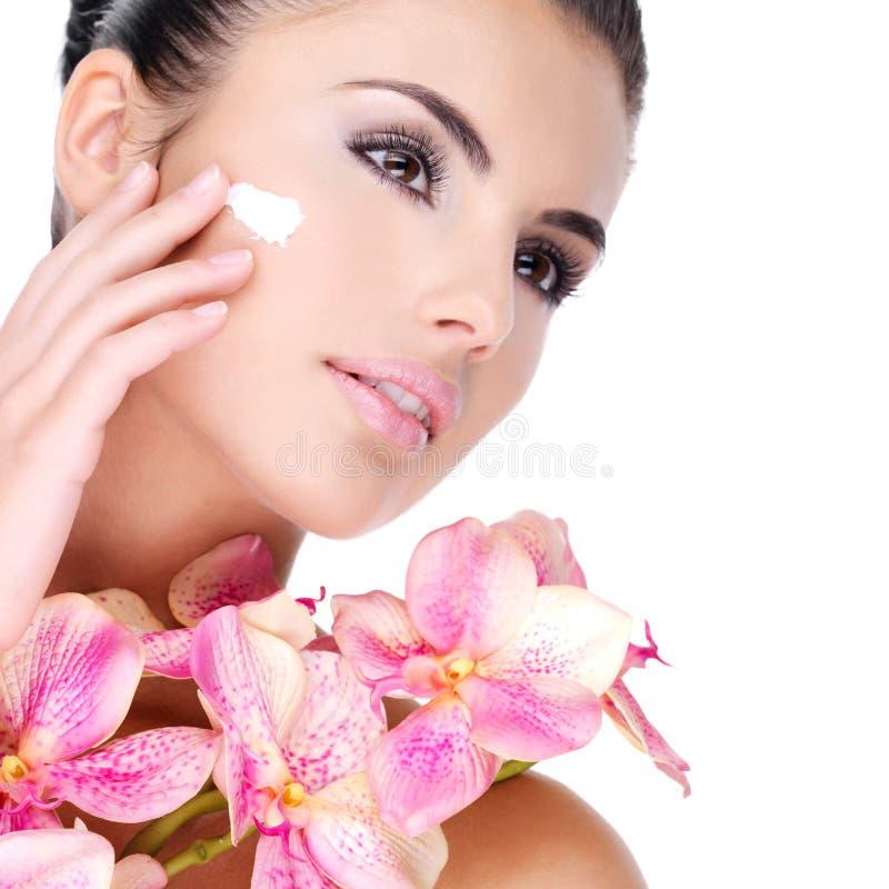 Donna che applica crema cosmetica sul fronte con i fiori rosa sul corpo fotografia stock libera da diritti