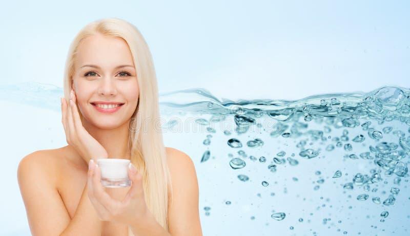 Donna che applica crema d'idratazione alla sua pelle del fronte fotografia stock