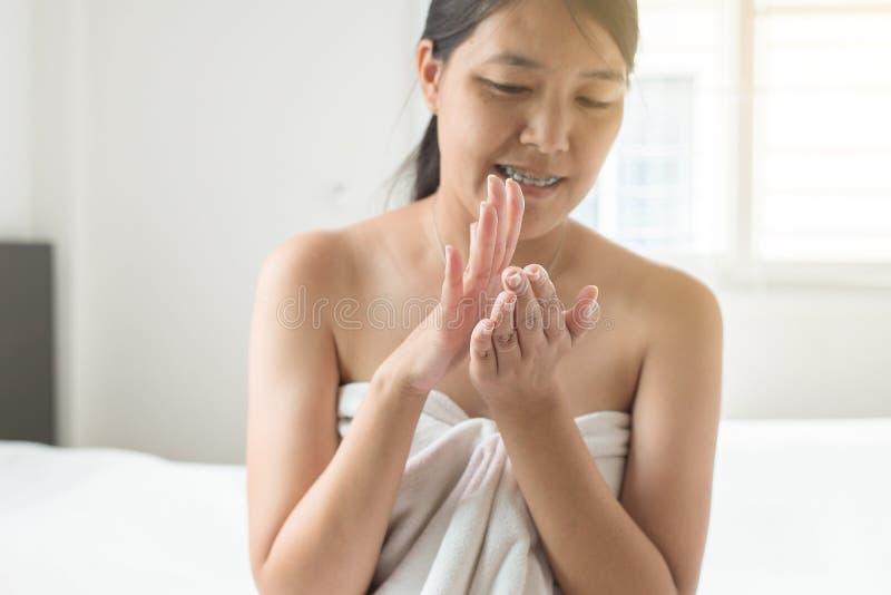 Donna che applica crema d'idratazione sulle mani, sul concetto sano e sulla pelle immagini stock libere da diritti