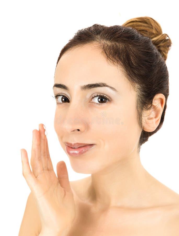 Donna che applica crema facciale immagini stock libere da diritti