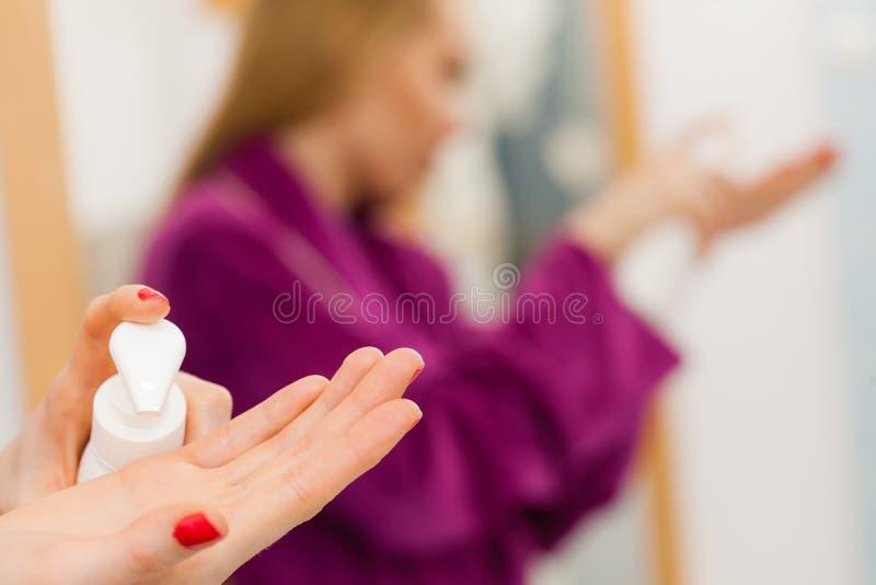 Donna che applica crema per le mani sulle mani immagini stock libere da diritti