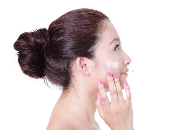 Donna che applica crema sul fronte nel profilo fotografia stock