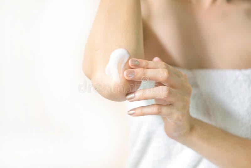 Donna che applica la crema del gomito, lozione immagini stock libere da diritti