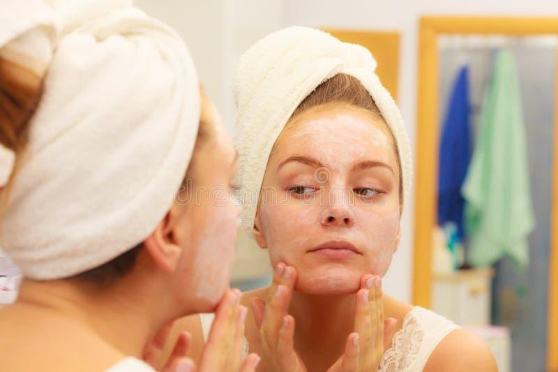 Donna che applica la crema della maschera sul fronte in bagno fotografia stock libera da diritti