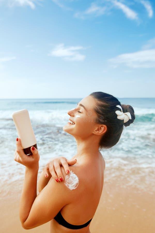 Donna che applica la crema della protezione solare sulla spalla abbronzata Skincare Suncream di protezione di Sun del corpo immagine stock libera da diritti