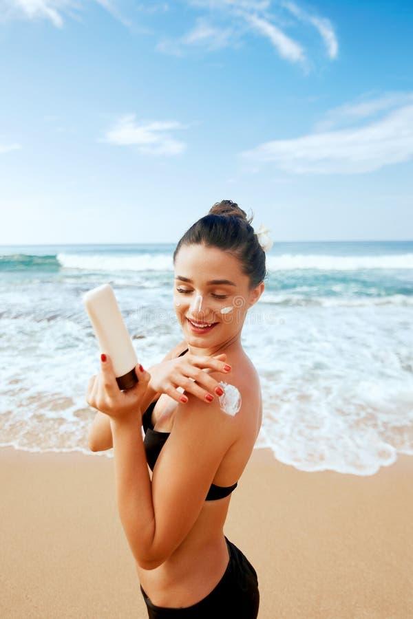 Donna che applica la crema della protezione solare sulla spalla abbronzata Skincare Suncream di protezione di Sun del corpo immagini stock libere da diritti