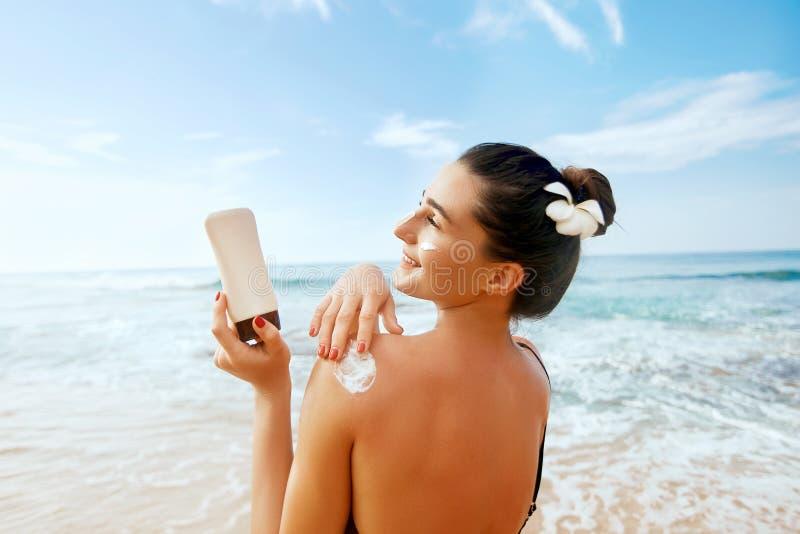 Donna che applica la crema della protezione solare sulla spalla abbronzata Skincare Suncream di protezione di Sun del corpo fotografia stock