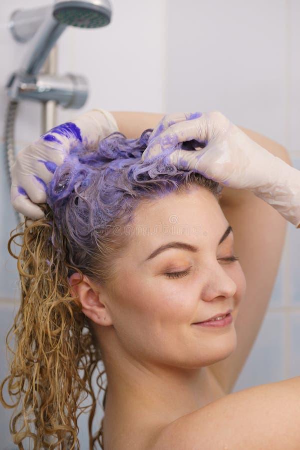Donna che applica lo sciampo del toner sui suoi capelli fotografie stock libere da diritti