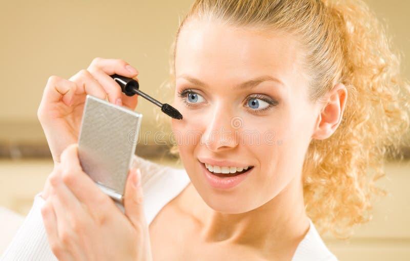 Donna che applica mascara fotografia stock