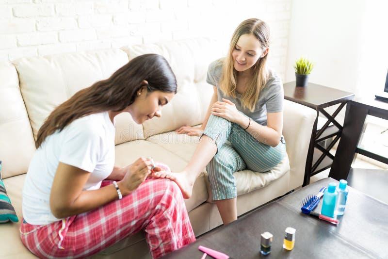 Donna che applica Nailpolish sulle unghie del piede del ` s dell'amico durante lo Sleepover fotografia stock libera da diritti