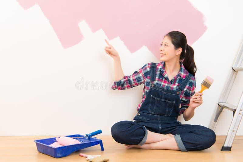 Donna che applica pittura rosa e che indica presentazione immagine stock libera da diritti