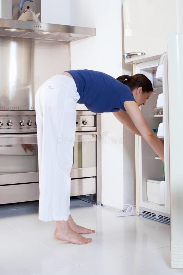 Donna che apre il frigorifero immagine stock