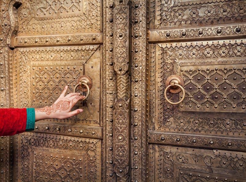 Donna che apre porta dorata a Jaipur fotografia stock libera da diritti