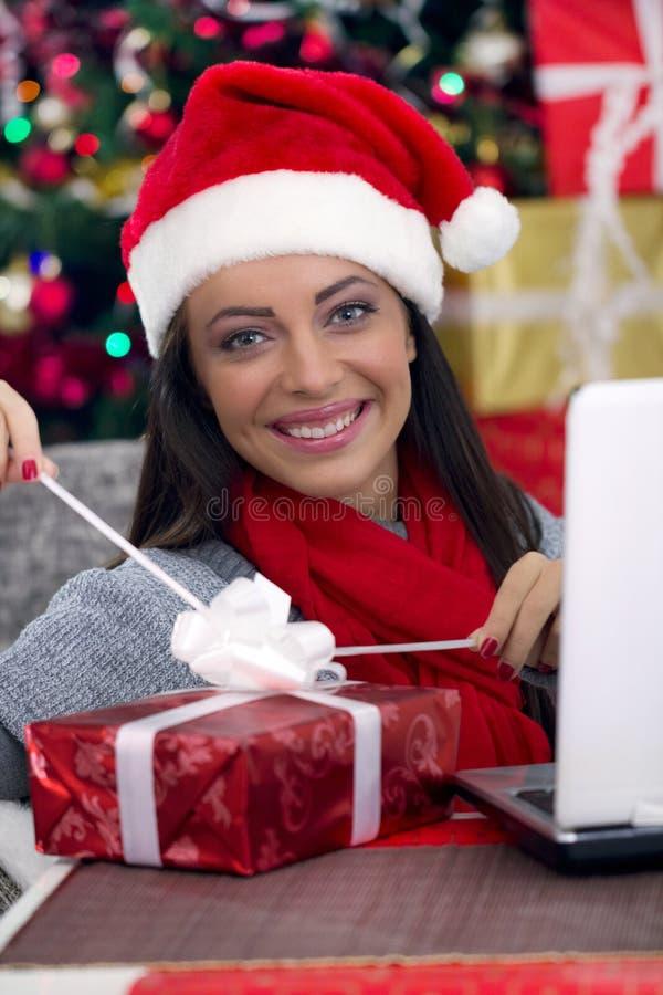 Donna che apre un regalo sulla notte di natale immagini stock libere da diritti