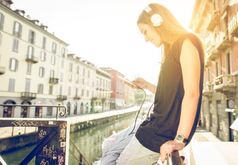 Donna che ascolta la musica con la cuffia avricolare e lo smartphone a Milano fotografie stock