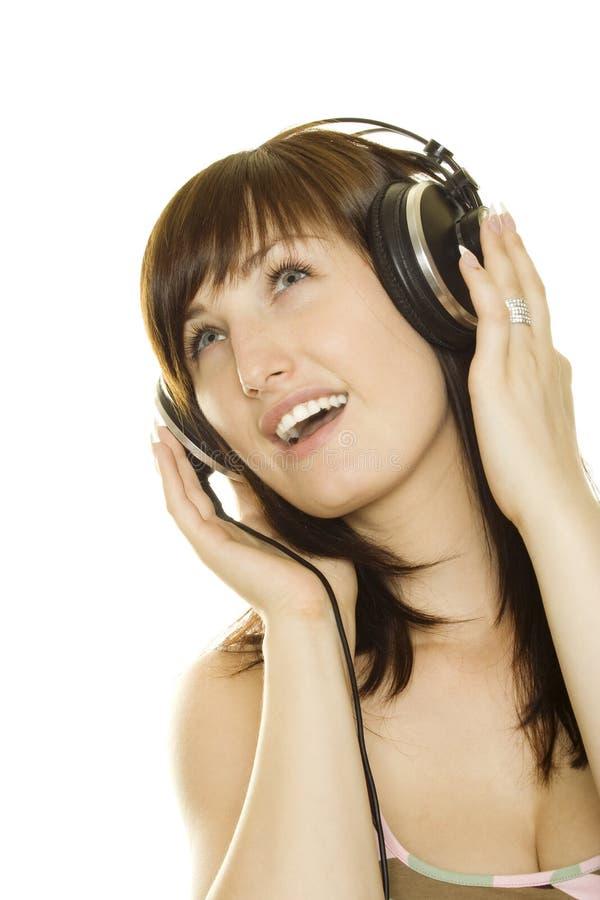 Donna che ascolta la musica e che canta fotografia stock