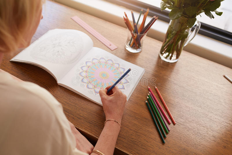 Donna che assorbe libro da colorare per gli adulti fotografia stock