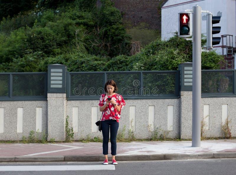 Donna che attraversa la via su luce rossa fotografia stock