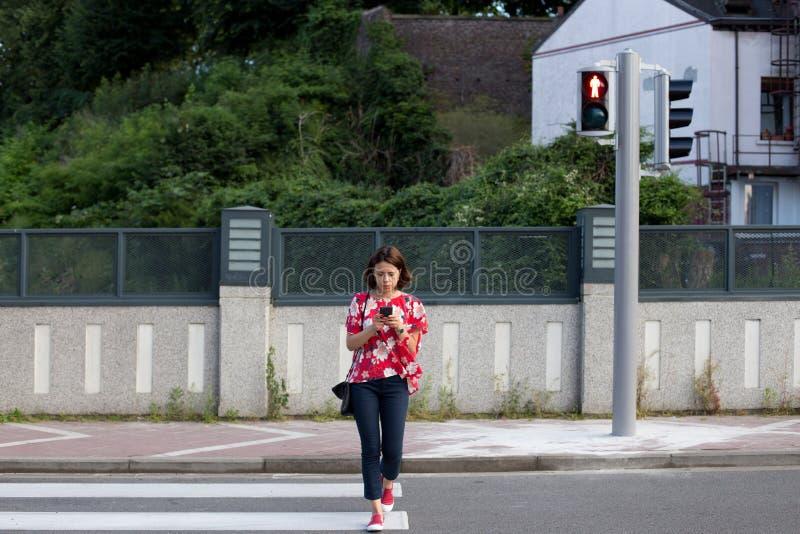 Donna che attraversa la via su luce rossa immagini stock libere da diritti