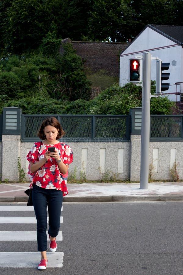 Donna che attraversa la via su luce rossa fotografie stock libere da diritti