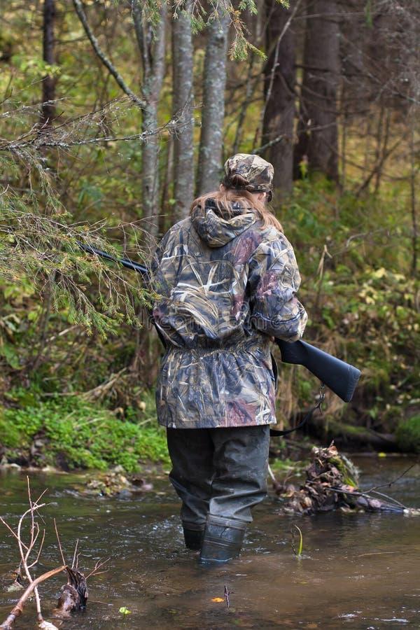 Donna che attraversa piccolo fiume sulla caccia fotografie stock