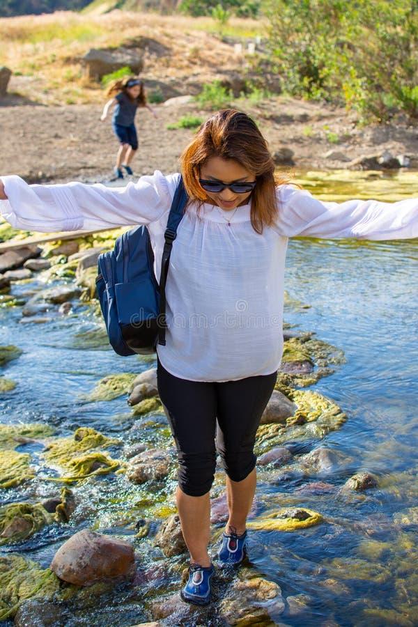 Donna che attraversa una corrente con la figlia che gioca in una corrente o in un fiume fotografie stock