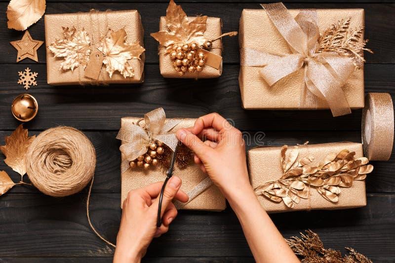 Donna che avvolge i regali di Natale sopra fondo di legno immagini stock libere da diritti