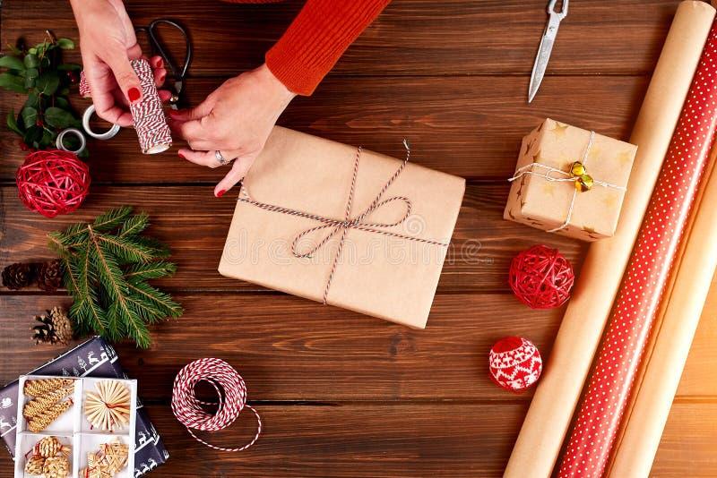 Donna che avvolge il contenitore di regalo con la decorazione degli oggetti sulla tavola di legno, fine su, vista superiore immagini stock libere da diritti