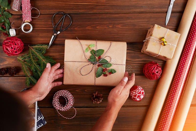 Donna che avvolge il contenitore di regalo con la decorazione degli oggetti sulla tavola di legno, fine su, vista superiore fotografie stock