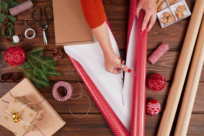 Donna che avvolge il contenitore di regalo con la decorazione degli oggetti sulla tavola di legno, fine su, vista superiore fotografie stock libere da diritti
