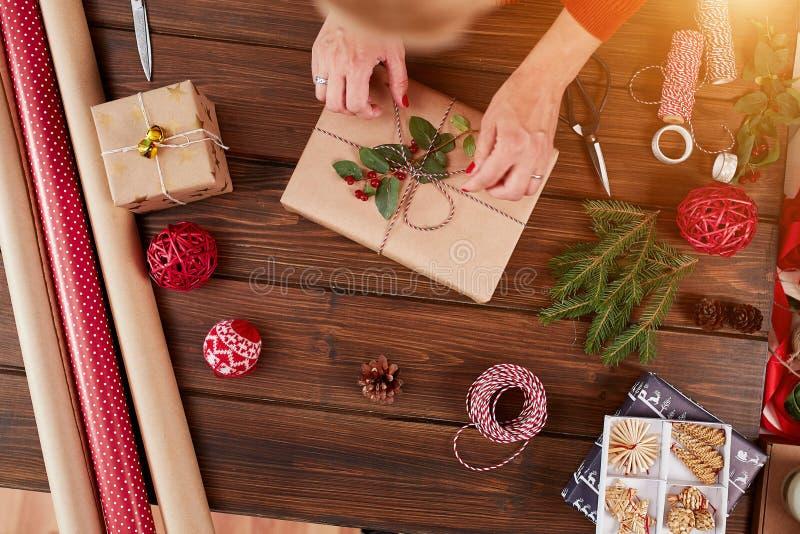 Donna che avvolge il contenitore di regalo con la decorazione degli oggetti sulla tavola di legno, fine su, vista superiore fotografia stock