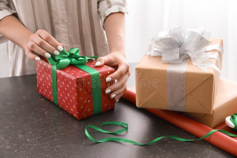 Donna che avvolge il contenitore di regalo di Natale alla tavola fotografia stock