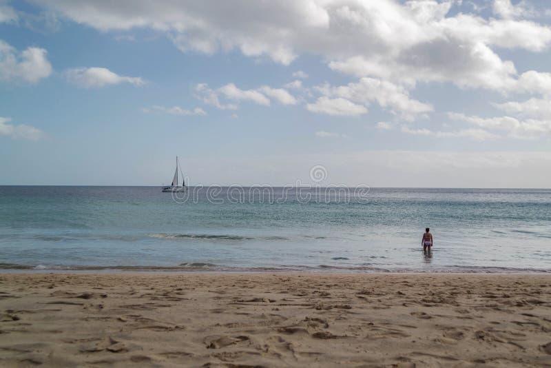 Donna che bagna nel mare, spiaggia giallo sabbia, con la barca a vela su Th immagine stock
