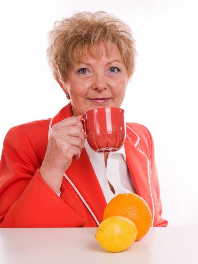 Donna che beve il succo di arancia immagine stock