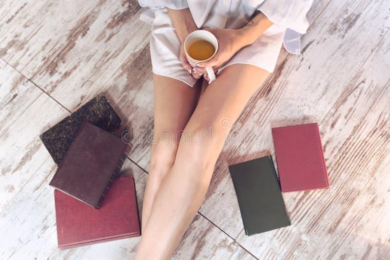 Donna che beve una tazza di tè nel rilassamento fotografia stock libera da diritti