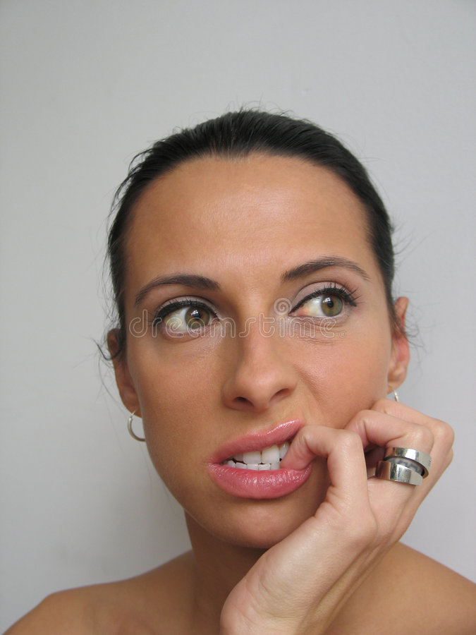 Donna che bitting il suo chiodo fotografia stock