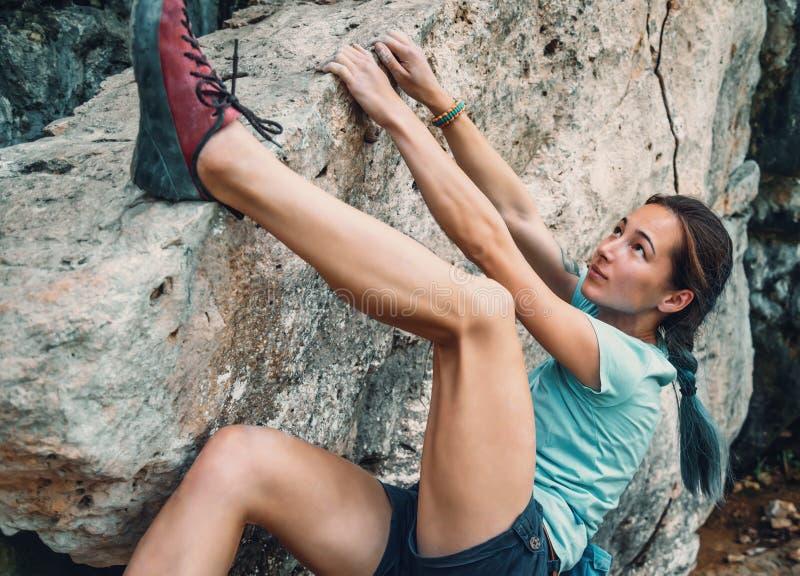 Donna che bouldering la pietra rocciosa immagine stock libera da diritti