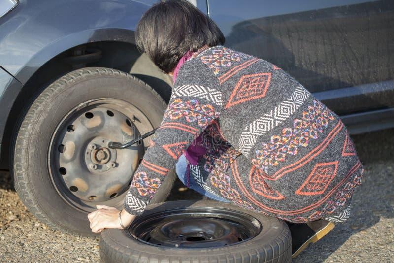 Donna che cambia una ruota su un'automobile sulla strada vuota fotografia stock
