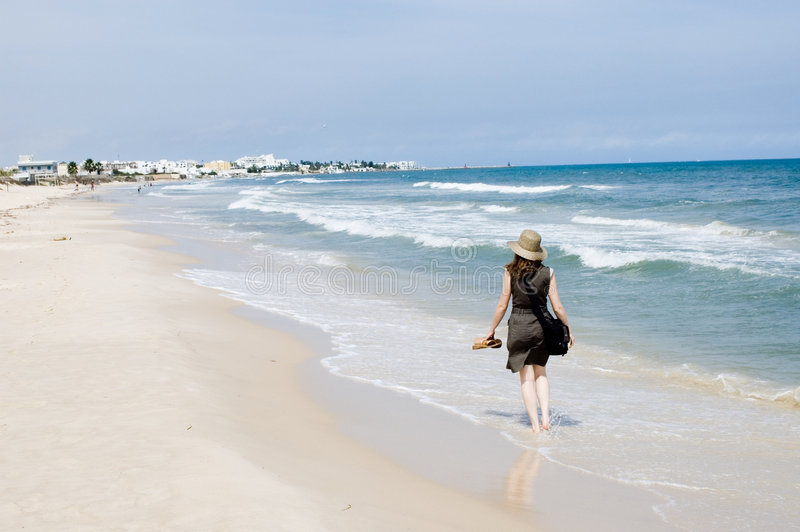 Donna che cammina alla spiaggia del mare immagine stock