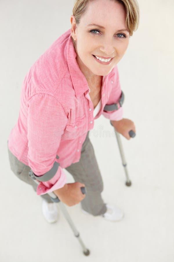Donna che cammina con le grucce immagine stock