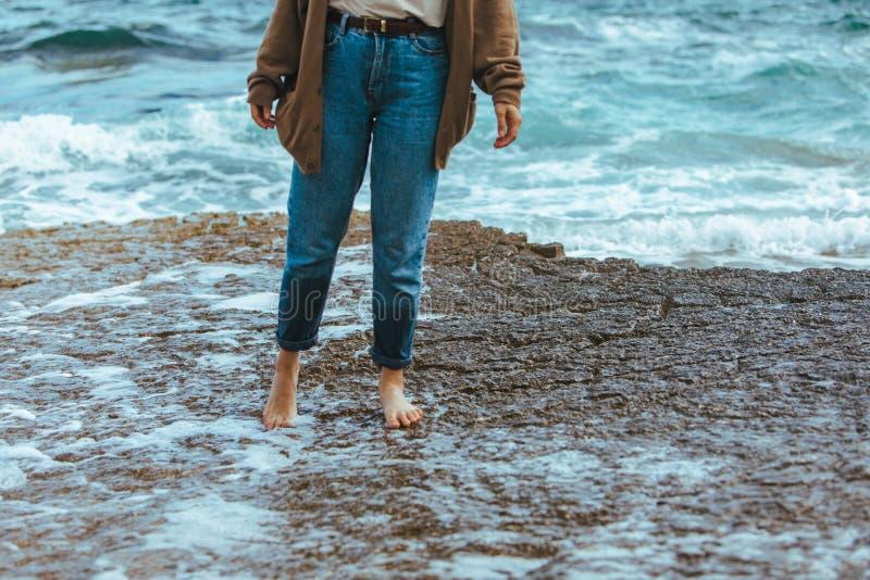 donna che cammina dai jeans bagnati scalzi della spiaggia rocciosa fotografie stock