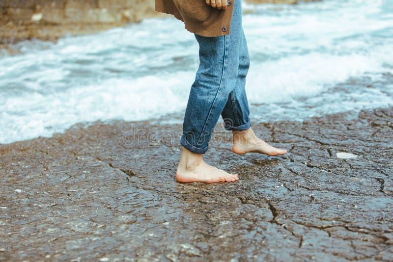 donna che cammina dai jeans bagnati scalzi della spiaggia rocciosa fotografia stock libera da diritti